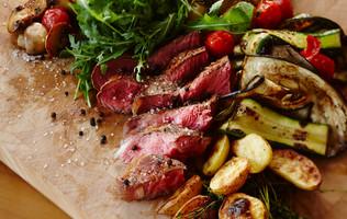 Fleisch und Gemüse auf einem Holzbrett im Victoria-Jungfrau Grand Hotel & Spa in Interlaken