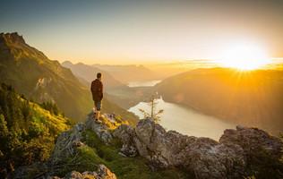 Wanderer geniesst den Sonnenuntergang über dem Thuner- und Brienzersee. Die Naturlandschaft ist in goldenes Licht getaucht.